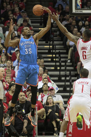 Photo - Oklahoma City Thunder forward Kevin Durant reaches for a rebound against Houston Rockets forward Terrence Jones, 6, during an NBA basketball game in Houston Friday, April 4, 2014.   (AP Photo/Richard Carson)