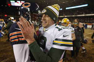 Photo - Green Bay Packers quarterback Aaron Rodgers (12) talks to Chicago Bears quarterback Jay Cutler after their NFL football game, Sunday, Dec. 29, 2013, in Chicago. The Packers won 33-28 to capture the NFC North title. (AP Photo/Charles Rex Arbogast)