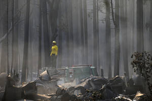 Photo - A firefighter stands on top of a fire truck at a campground destroyed by the Rim Fire near Yosemite National Park, Calif., on Monday, Aug. 26, 2013. Crews working to contain one of California's largest-ever wildfires gained some ground Monday against the flames threatening San Francisco's water supply, several towns near Yosemite National Park and historic giant sequoias. (AP Photo/Jae C. Hong)