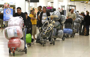 Photo - FILE - In this Dec. 19, 2011, file photo, travelers wait in line with their luggage at Miami International Airport before traveling Cuba in Miami. The door for travel to Cuba cracked open during President Barack Obama's first term. Cuban-Americans can now visit family on the island as often as they like. Americans can travel legally as part of an academic or religious trip. Perhaps it's for this reason that Obama's standing with the Cuban-American community in Florida stayed largely steady on Election Day, even though the modest openings with Cuba have riled some of South Florida's more conservative exiles. Exit polling showed that 49 percent of Cuban-Americans voted for the Democrat, roughly the same percentage as four years ago. (AP Photo/Lynne Sladky, File)
