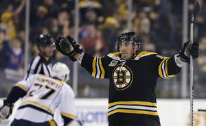 Photo - Boston Bruins left wing Brad Marchand sticks out his tongue as he celebrates his goal during overtime against the Nashville Predators during an NHL hockey game, Thursday, Jan. 2, 2014, in Boston.  The Bruins won 3-2. (AP Photo/Charles Krupa)