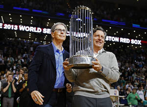Photo - Boston Red Sox owner John Henry, left, and chairman Tom Werner hold the World Series trophy before an NBA basketball game between the Boston Celtics and the Milwaukee Bucks in Boston, Friday, Nov. 1, 2013. (AP Photo/Michael Dwyer)
