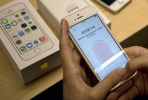 Photo - FILE - In this Sept. 20, 2013 file photo, a customer configures the fingerprint scanner technology built into the Apple iPhone 5S at an Apple store in Wangfujing shopping district in Beijing. Beyond unlocking the phone, the fingerprint can be used to authenticate the purchase of apps and content within apps. This fall, Apple will begin letting outside developers use the fingerprint ID as part of their apps. (AP Photo/Andy Wong, File)