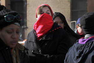 Photo -   Nicole Vasquez uses a scarf to keep warm while waiting for food at an American Red Cross station in the Coney Island section of Brooklyn, Monday, Nov. 5, 2012 in New York. The region is still cleaning up a week after Superstorm Sandy. (AP Photo/Mark Lennihan)