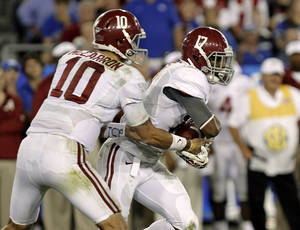 Photo - Alabama quarterback A.J. McCarron (10) hands off to running back Kenyan Drake (17) during the second quarter of an NCAA college football game against Kentucky in Lexington, Ky., Saturday, Oct. 12, 2013. (AP Photo/Garry Jones)