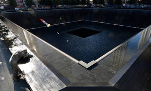 Photo -   Scott Willens, who joined the United States Army three days after the attacks on Sept. 11, 2001, pauses by the South Pool of the World Trade Center Memorial during the 11th anniversary observance, Tuesday, Sept. 11, 2012 in New York. (AP Photo/Justin Lane, Pool)
