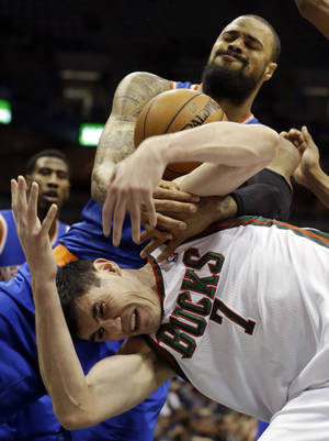 Photo - New York Knicks' Tyson Chandler, top, and Milwaukee Bucks' Ersan Ilyasova (7) battle for a rebound during the first half of an NBA basketball game on Wednesday, Dec. 18, 2013, in Milwaukee. (AP Photo/Morry Gash)