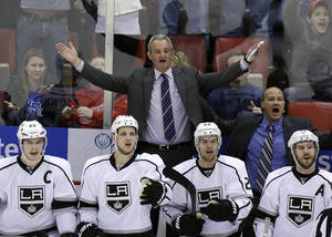 Photo - Los Angeles Kings head coach Darryl Sutter, top, reacts after the Detroit Red Wings were awarded the tying goal during the third period of an NHL hockey game in Detroit, Saturday, Jan. 18, 2014. (AP Photo/Carlos Osorio)