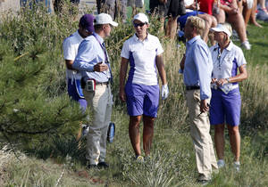 Photo - Europe's Carlota Ciganda, center, from Spain is flanked by officials after she lost a ball on the 15th hole during fourball matches at the Solheim Cup golf tournament on Friday, Aug. 16, 2013, in Parker, Colo. (AP Photo/Ed Andrieski)