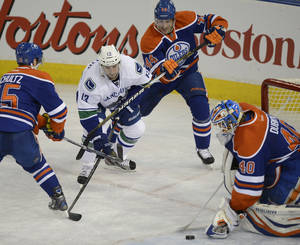 Photo - Edmonton Oilers goalie Devan Dubnyk stops the puck while the Vancouver Canucks' Steve Pinizzotto, 13 tries to get his stick on it during first period NHL hockey action in Edmonton, on Saturday, April 27, 2013.  (AP Photo/The Canadian Press, Ian Jackson)