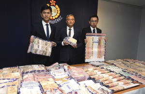 Photo - In this June 9, 2014 photo, officers from Hong Kong Police's organized crime and triad bureau, display stacks of cash seized after they launched an operation with counterparts in mainland China to smash a cross-border illegal gambling syndicate days before the start of the World Cup in Brazil. As teams battle for glory at football's biggest event, the biggest winners may be Asia's illegal bookmakers, who are thriving because demand from sports fans to place bets is surging but legal options are few. Government monopoly operators offer legal sports betting in a handful of Asian jurisdictions but there are thousands more black market operators. Asia accounts for just over half of the nearly $700 billion in illegal bets placed worldwide each year, according to a sports monitoring group.  (AP Photo)