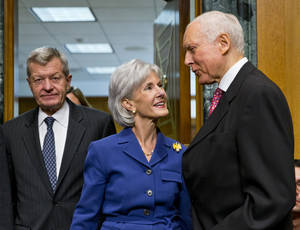 Photo - Health and Human Services Secretary Kathleen Sebelius, center, is greeted by Sen. Orrin Hatch, R-Utah, ranking Republican on the Senate Finance Committee, right, as she is escorted by the committee's Chairman Sen. Max Baucus, D-Mont., on Capitol Hill in Washington, Wednesday, Nov. 6, 2013, prior to testifying before the committee's hearing on the difficulties plaguing the implementation of the Affordable Care Act. The massive failure at healthcare.gov website is getting new criticism for lack of proper cybersecurity protections.  (AP Photo/J. Scott Applewhite)