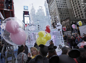 "Photo -   People with mouse ear caps and balloons gather near a three-story castle mad of ice in New York's Times Square, Wednesday, Oct. 17, 2012. On Wednesday, Disney announced a new program for 2013, ""Limited Time Magic,"" in which guests will encounter surprise weekly themes at Disney parks in Florida and California. The program was described as ""52 weeks of magical experiences big and small that appear, then disappear as the next special surprise debuts."" For example, a weeklong Valentine's Day celebration might include pink lighting on Disney castles, surprise meet-and-greets with Disney characters and candlelit dinners for lovebirds. (AP Photo/Richard Drew)"