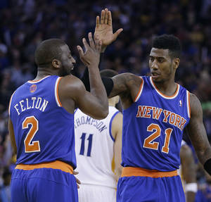 Photo - New York Knicks' Raymond Felton, left, celebrates with Iman Shumpert (21) in the final seconds of an NBA basketball game against the Golden State Warriors Sunday, March 30, 2014, in Oakland, Calif. (AP Photo/Ben Margot)