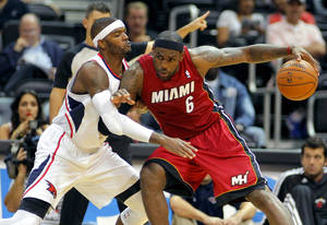 Photo -   Miami Heat forward LeBron James (6) is defended by Atlanta Hawks' Josh Smith in the first half of a preseason NBA basketball game, Sunday, Oct. 7, 2012, in Atlanta. (AP Photo/Todd Kirkland)
