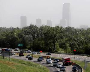 photo - Traffic flows along Broadway Extension as winds from a cold front make the downtown skyline hard to see in Oklahoma City, Friday, September, 7, 2012. Photo by Bryan Terry