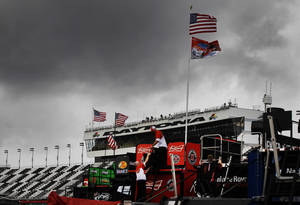 Photo - Crew members work on pit road under threatening skies during practice for Sunday's NASCAR Daytona 500 Sprint Cup series auto race in Daytona Beach, Fla., Friday, Feb. 21, 2014. (AP Photo/Terry Renna)