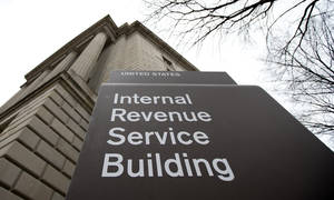 photo - This photo taken March 2, 2013, shows the Internal Revenue Service building at the Federal Triangle complex in Washington, Saturday, March 2, 2013. According to projections by the Tax Policy Center, a research organization based in Washington, wealthy families are paying some of their biggest federal tax bills in decades, even as the rest of the population continues to pay at historically low rates. And a new analysis by the Congressional Budget Office shows that average tax bills for high-income families have rarely been higher since the Congressional Budget Office began tracking the data in 1979, while middle- and low-income families aren't paying as much as they used to. (AP Photo/ roomManuel Balce Ceneta)