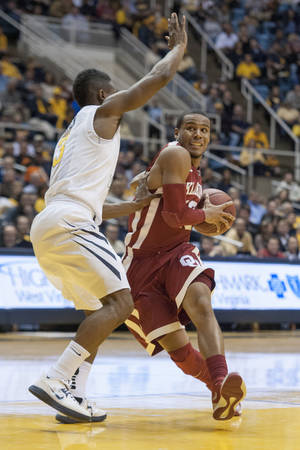 Photo - Oklahoma's Jordan Woodard, right, looks to drive by West Virginia's Juwan Staten during the first half of an NCAA college basketball game on Wednesday, Feb. 5, 2014, in Morgantown, W.Va. (AP Photo/Andrew Ferguson)