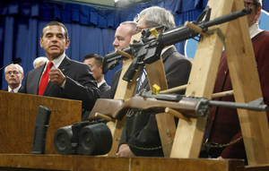 photo - Los Angeles Mayor Antonio Villaraigosa, left, glances over to a pair of semi-automatic rifles as he discusses his support for a package of proposed gun control legislation at a Capitol news conference in Sacramento,  Calif., Thursday, Feb. 7, 2013. Senate Democrats unveiled a package of 10 proposed laws designed to close loopholes in existing gun regulations, keep firearms and ammunition out of the hands of dangerous person and strengthen education relating to firearms and gun ownership.(AP Photo/Rich Pedroncelli)