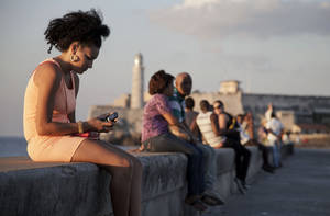 "Photo - In this March 11, 2014 photo, a woman uses her cellphone as she sits on the Malecon in Havana, Cuba. The U.S. Agency for International Development masterminded the creation of a ""Cuban Twitter,"" a communications network designed to undermine the communist government in Cuba, built with secret shell companies and financed through foreign banks, The Associated Press has learned. The project, which lasted more than two years and drew tens of thousands of subscribers, sought to evade Cuba's stranglehold on the Internet with a primitive social media platform. (AP Photo/Franklin Reyes)"