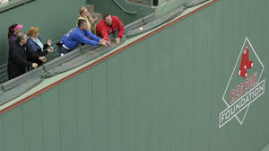 Photo - Fans try to catch balls hit over the Green Monster left field wall as the St. Louis Cardinals take batting practice Tuesday, Oct. 22, 2013, in Boston. The Cardinals are scheduled to play the Boston Reds Sox in Game 1 of baseball's World Series on Wednesday. (AP Photo/Charlie Riedel)