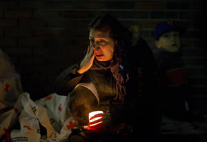 Photo - A mourner weeps while listening to President Barack Obama speak on a loudspeaker while sitting outside a memorial at Newtown High School for the victims of the Sandy Hook Elementary School shooting, Sunday, Dec. 16, 2012, in Newtown, Conn. (AP Photo/David Goldman)
