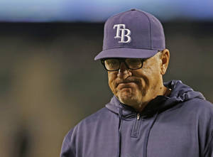 Photo - Tampa Bay Rays manager Joe Maddon walks to the dugout after a pitching change in the sixth inning of a baseball game against the Seattle Mariners, Saturday, Sept. 7, 2013, in Seattle. (AP Photo/Ted S. Warren)
