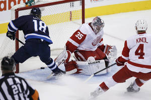 Photo - Winnipeg Jets' Bryan Little (18) scores on Detroit Red Wings' goaltender Jimmy Howard (35) and Jakub Kindl (4) during first period NHL action in Winnipeg on Monday, Nov. 4, 2013. (AP Photo/The Canadian Press, John Woods)