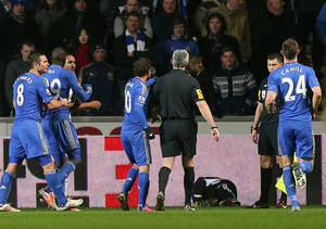 photo - A ball boy, third right, lies on the pitch following an incident Chelsea's Eden Hazard, not pictured,  as referee Chris Foy, center in black, makes his way over to calm the situation during the English League Cup second leg semi-final soccer match between Chelsea and Swansea City at the Liberty Stadium, Swansea, Wales, Wednesday Jan. 23, 2013.  Hazard received a red card for the incident. (AP Photo/PA, Nick Potts) UNITED KINGDOM OUT  NO SALES  NO ARCHIVE