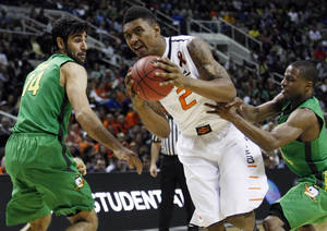 Photo - OSU's Le'Bryan Nash drives through Oregon's Arsalan Kazemi and Johnathan Loyd in the second round of the NCAA Basketball tournament in San Jose, CA, Mar. 21, 2013. STEPHEN PINGRY/Tulsa World