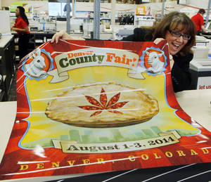 Photo - Dana Cain, director of the Denver County Fair, shows a poster advertising the fair at a print shop in Denver, Monday Jan. 27, 2014.  Colorado's Denver County is adding cannabis-themed contest to its 2014 summer fair. (AP Photo/Ed Andrieski)