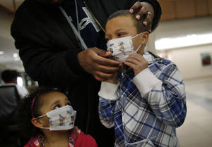 Photo - Here Damien Dancy puts masks on his children Damaya, 3, left, and Damien, 7, on Wednesday, Jan. 9, 2013 at Sentara Princess Anne Hospital in Virginia Beach, Va.   Hospitals in Hampton Roads are urging patients and visitors to wear a mask at their facilities to help stop the spread of the flu. The recommendation was issued Wednesday by more than two dozen medical centers. In a joint statement, the hospitals said the recommendation applies to hospitals, urgent care centers and branch clinics, among others. (AP Photo/The Virginian-Pilot, Stephen M. Katz)