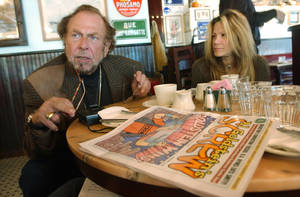 Photo - FILE - In this Oct. 28, 2003 file photo, Screw magazine publisher Al Goldstein sits for an interview at a coffee shop in New York with his longtime assistant Terre Galizio. Goldstein, the bird-flipping publisher who helped break down legal barriers against pornography and raged against politicians, organized religion and anything that even suggested good taste, died at a Brooklyn hospice Thursday, Dec. 19, 2013 after a long illness, according to a friend, attorney Charles C. DeStefano. He was 77. (AP Photo/Mary Altaffer, File)