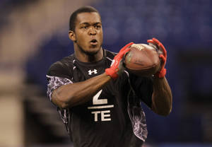 Photo - Tulsa tight end Charles Clay makes a catch as he runs a drill at the NFL football scouting combine in Indianapolis, Saturday, Feb. 26, 2011. (AP Photo/Michael Conroy)