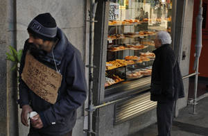"""Photo - A man begs money with a banner reading """"I have three kids, help me please, thank you, happy christmas, god bless you"""" as a woman looks at  'Three Kings' cakes outside  a bakery shop in Madrid, Sunday, Jan. 6, 2013. (AP Photo/Andres Kudacki)"""