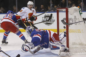 Photo - Calgary Flames' Curtis Glencross, second from left, scores a goal against New York Rangers goalie Henrik Lundqvist, of Sweden, during the first period of an NHL hockey game Sunday, Dec. 15, 2013, in New York. (AP Photo/Jason DeCrow)