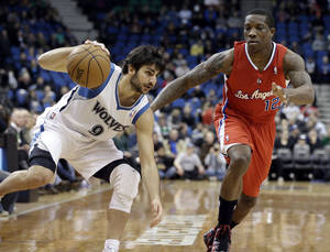 Photo - Minnesota Timberwolves' Ricky Rubio of Spain, left, maintains his balance as he drives past Los Angeles Clippers' Eric Bledsoe in the first half of an NBA basketball game Wednesday, Jan. 30, 2013 in Minneapolis. (AP Photo/Jim Mone)