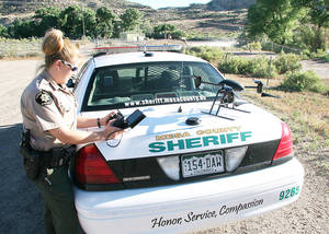photo - Deputy Amanda Hill of the Mesa County sheriff's office in Colorado prepares to use a Draganflyer X6 drone equipped with a video camera to help search for a suspect in a knife attack in Mesa County, Colo. AP FILE PHOTO