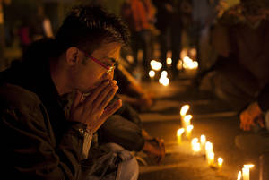photo - An Indian participates in a candle-lit vigil to mourn the death of a gang rape victim in New Delhi, India, Saturday, Dec. 29, 2012. Indian police charged six men with murder on Saturday, adding to accusations that they beat and gang-raped the woman on a New Delhi bus nearly two weeks ago in a case that shocked the country. The murder charges were laid after the woman died earlier Saturday in a Singapore hospital where she has been flown for treatment. (AP Photo/ Dar Yasin)