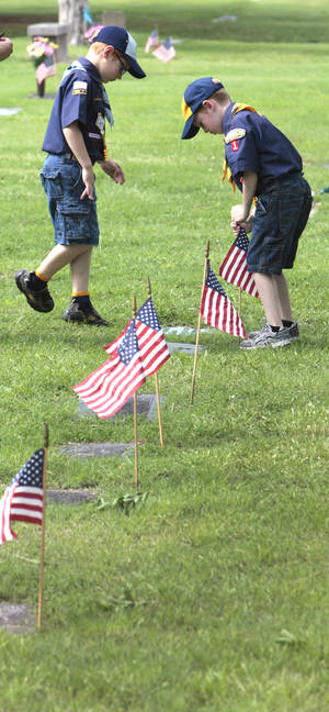 Photo - Boy Scouts place American flags on the graves of veterans at Memorial Park Cemetery.  Photo by David McDaniel, The Oklahoman <strong>David McDaniel - The Oklahoman</strong>