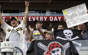 Photo - Pittsburgh Pirates fans celebrate after the Pirates defeated the Cincinnati Reds 8-3 in a baseball game, Saturday, Sept. 28, 2013, in Cincinnati. The two teams will play a wild card playoff game Tuesday in Pittsburgh. (AP Photo/Al Behrman)