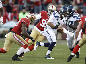 Photo - Seattle Seahawks quarterback Russell Wilson (3) keeps the ball as San Francisco 49ers inside linebacker NaVorro Bowman, and outside linebacker Aldon Smith, second from left, close in during the second half of an NFL football game, Sunday, Dec. 8, 2013, in San Francisco. (AP Photo/Ben Margot)