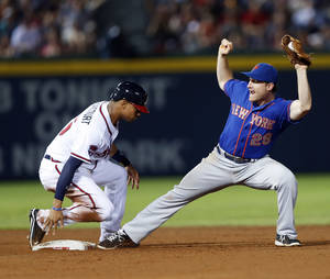 Photo - Atlanta Braves' Christian Bethancourt (25) beats New York Mets second baseman Daniel Murphy (28) to the bag as he advances to second base on a B.J. Upton single in the seventh inning of a baseball game in Atlanta, Monday, June 30, 2014.  (AP Photo/John Bazemore)