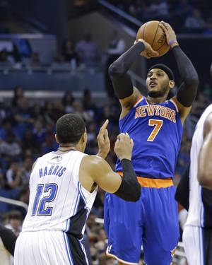 Photo - New York Knicks' Carmelo Anthony (7) shoots over Orlando Magic's Tobias Harris (12) in the first half of an NBA basketball game in Orlando, Fla., Monday, Dec. 23, 2013. (AP Photo/John Raoux)