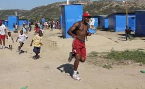 Photo - OU receiver Justin McCay runs on a recent trip to Haiti. Photo by Michael Davis.