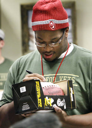Photo - OU: University of Oklahoma football player Adam Shead autographs a football as players visit the Veteran's Center with Quinton Carter's SOUL Foundation  on Thursday, December 16, 2010, in Norman, Okla.   Photo by Steve Sisney, The Oklahoman ORG XMIT: KOD