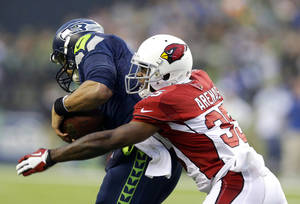 Photo - Seattle Seahawks quarterback Russell Wilson, left, is sacked by Arizona Cardinals' Javier Arenas in the second half of an NFL football game, Sunday, Dec. 22, 2013, in Seattle. The Cardinals won 17-10. (AP Photo/Elaine Thompson)