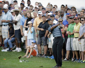 Photo - Tiger Woods hits a fairway shot near the gallery on the first hole during the second round of The Barclays golf tournament on Friday, Aug. 23, 2013, in Jersey City, N.J. (AP Photo/Mel Evans)