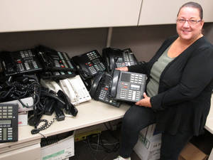 photo -   In this Monday, Sept. 17, 2012 photo, Mary Morgan, a Nassau County information technology specialist, poses with the telephones she is assessing as part of a countywide efficiency effort in Mineola, N.Y. Nassau County is currently shutting off hundreds of unused telephone lines and reviewing their current stock of telephones as part of a cost-cutting initiative. (AP Photo/Frank Eltman)